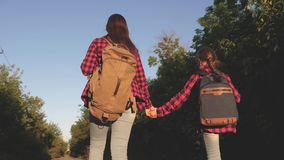 Teen girls travel and hold hands. Hiker girl. Children travellers. Girls with backpacks are on the country road in the stock video