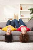 Teen girls upside down. Teen girls lying on couch upside down, listening to music in earbuds, eyes closed Royalty Free Stock Images