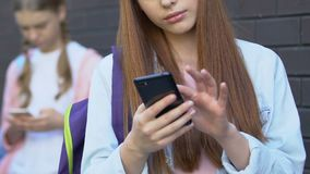 Teen girls using cellphones, chatting in social network, internet addiction. Stock footage stock video footage