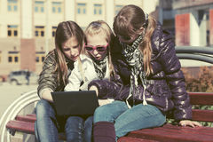 Teen girls using laptop on the bench in city street Stock Photo