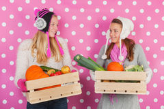 Teen girls with vegetables in winter. Teen girls in front of pink background with vegetables in winter Royalty Free Stock Images