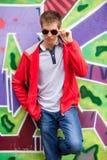 teen in glasses standing near graffiti wall. Stock Photos