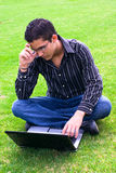 Teen with glasses using laptop. Teen student with glasses and laptop outdoors stock photo