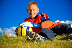 Teen goalie. Teen laying on grass area with soccer ball Royalty Free Stock Photo