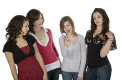 Teen gossip. Four teenage girls standing with cellphone Stock Photography