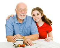 Teen & Grandpa. Teen girl and her grandfather at the table filling out paperwork together.  Isolated on white Stock Photos