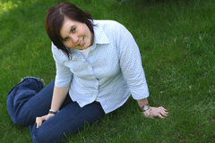 Teen on a grass. A young smiling girl sitting on a grass Royalty Free Stock Images