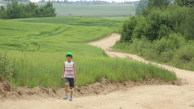 Teen with a graze on knee walking along a country sand road near the field stock footage