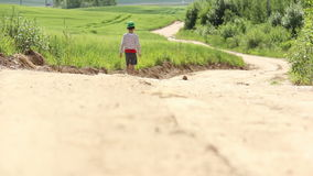 Teen with a graze on knee walking along a country sand road near the field stock video footage