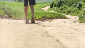 Teen with a graze on knee walking along a country sand road near the field stock video