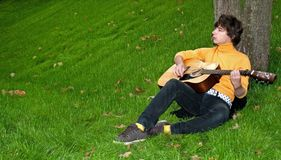 Teen with guitar on grass Stock Image