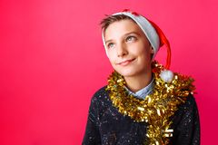 Teen guy dressed in Santa hat and with tinsel around his neck ma royalty free stock images