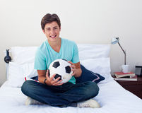 Teen guy holding a soccer ball in his bedroom Royalty Free Stock Photo