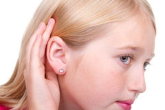 Teen with hand to ear listening Royalty Free Stock Photography