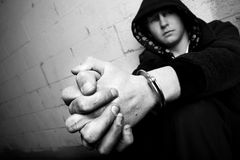 Teen in handcuffs. Young teen against wall with dirty hands and handcuffs, converted to black and white with slight added grain. focus on cuffs stock image