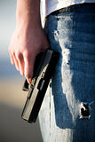 Teen with handgun. Teen male holding modern 9mm handgun, limited depth of field closeup royalty free stock photography