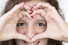 Teen with hands in heart shape. Teen with her hands held in a heart shape over her face Royalty Free Stock Photos