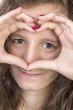 Teen with hands in heart shape. Teen with her hands held in a heart shape over her face Stock Image