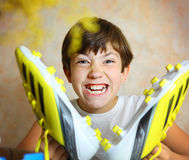 Teen handsome boy with brand new yellow football boots close up Stock Image