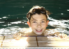 Teen happy boy in the swimming pool. Close up smiling portrait Royalty Free Stock Photo