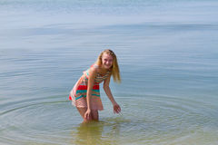 Teen happy girl in colorful dress posing in the sea Stock Images