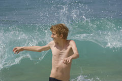 Teen having fun with high waves Royalty Free Stock Image