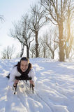 Teen having fun on sledge. Young joyful woman smiling in winter season Royalty Free Stock Images