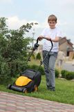 Teen helps mow the lawn Stock Photos