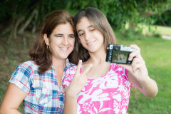 Teen and her young mother taking a self picture. Hispanic teenager and her young mother taking a self picture at a beautiful park Stock Image
