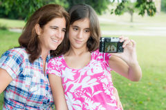 Teen and her young mother taking a self picture. Hispanic teenager and her young mother taking a self picture at a beautiful park Royalty Free Stock Photos