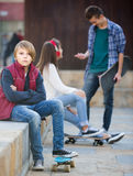 Teen and his friends after conflict outdoors Stock Photos