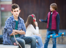 Teen and his friends after conflict outdoors Royalty Free Stock Images