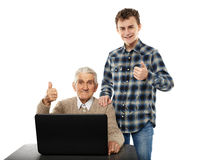 Teen with his granddad at laptop. Teenage boy teaching his grandfather how to use a laptop Stock Photo
