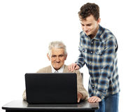 Teen with his granddad at laptop. Teenage boy teaching his grandfather how to use a laptop Stock Photos
