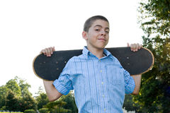 Teen with His Skateboard. A boy in his early teens happily standing with his skateboard Stock Images
