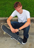 Teen and his skateboard in a casual pose. A teen sits on the curb and rests with his skateboard Stock Images