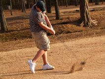 Teen Hitting the Ball. A young man hits the golf ball with sand in the air Stock Images
