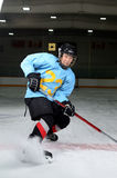 Teen Hockey Player. A Teen Age Hockey Player Makes Sharp Stop in the Rink royalty free stock images