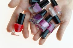 Teen holdind nail polish bottles into open hands Royalty Free Stock Images