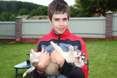 Teen holding a husky puppy. Royalty Free Stock Photography
