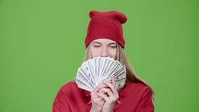 Teen is holding paper money in her hands. Green screen. Slow motion. Teen holds paper money in her hands, she won a jackpot in the lottery. Green screen. Slow stock video