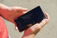 Teen is holding phone with broken screen after falling down. Teen is holding some black phone with broken screen after falling down royalty free stock photos