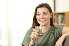 Teen holding a water glass looking at side at home Royalty Free Stock Photo