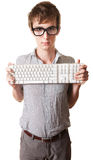 Teen Holds Computer Keyboard. Young Caucasian man holds computer keyword over white background Stock Image