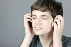 Teen Holds Headphones To Ears With Eyes Closed Stock Images