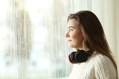 Teen at home looking outdoors in a rainy day. Side view portrait of a distracted teen at home looking outdoors in a rainy day Stock Photography