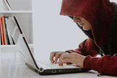 Teen in hoodie typing on laptop. Teen boy wearing red hoodie typing on laptop computer in home office Royalty Free Stock Photo