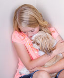 Teen hugging dog in corner. Sad teen in corner holding her shih tzu dog for comfort stock images