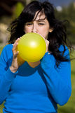Teen inflating yellow balloon. In the park Royalty Free Stock Photography