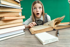 Teen interested in reading book with magnifier Stock Photos